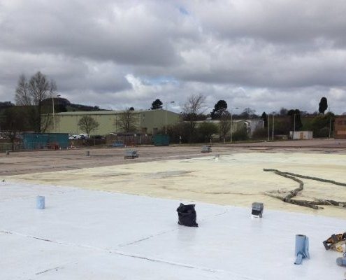 A Large Flat Commercial Roof During the Application of Prokol Primer Uni