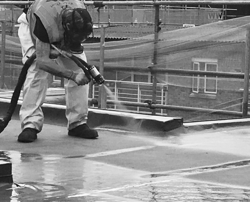 A Roofer Spraying Prokol Prokol Hotspray 260FR on a roof