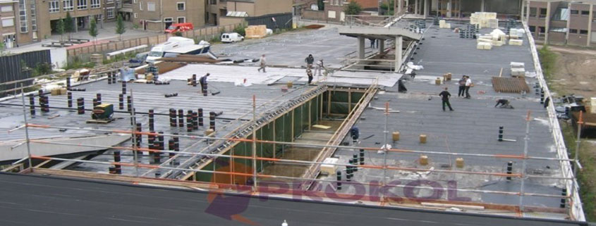 A Large Commercial Roof with workers applying Prokol Protection Coatings USA's Waterproof and Fire Retardant Hotspray Roofing Products